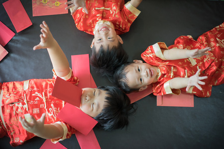 Photo pour Happy chinese new year. 3 cute asian little boys are playing red envelopes together on the bed. - image libre de droit