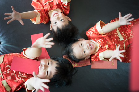 Foto de Happy chinese new year. 3 cute asian little boys are playing red envelopes together on the bed. There are Chinese blessing words Longevity, auspicious and wealthy in the Chinese suit. - Imagen libre de derechos