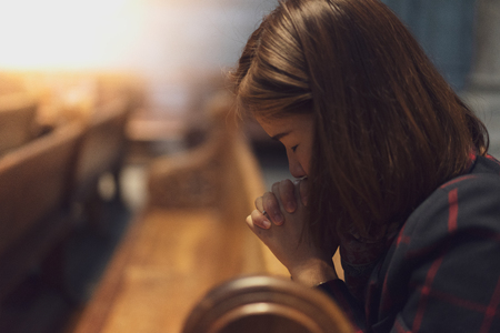 Foto de A Christian girl is sitting and praying with humble heart in the church. - Imagen libre de derechos
