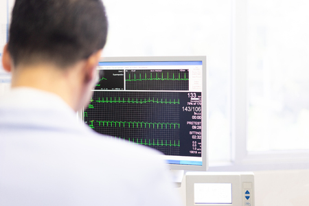 Foto de The doctor check heart rate and pulse of patient by running test for protect the heart attack at the hospital. - Imagen libre de derechos