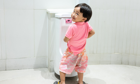 Foto de A boy is pissing himself in the bathroom. - Imagen libre de derechos