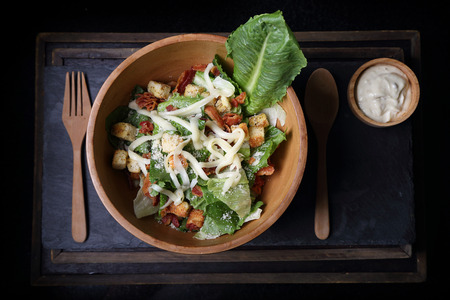 Photo pour Organic caesar salad in wodden bowl with caesar dressing. International food. - image libre de droit