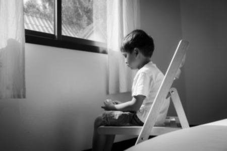 Blurry of little boy sitting alone on chair  at window in room,black and white