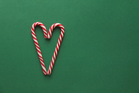 Photo pour Heart from Candy. Candy Canes Red-White in the Heart Form Lie on the Green Background, View From above. For your Decoration of Postcards, New Year and Christmas. Place for Text. Top view - image libre de droit