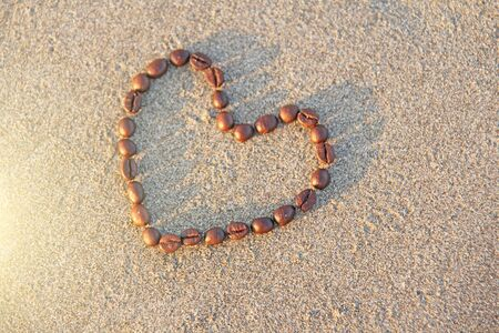 Photo pour Heart of coffee. Grains of coffee are laid out on sand in the form of heart. Love of coffee. Design with copy space. Top view. A frame of coffee. - image libre de droit