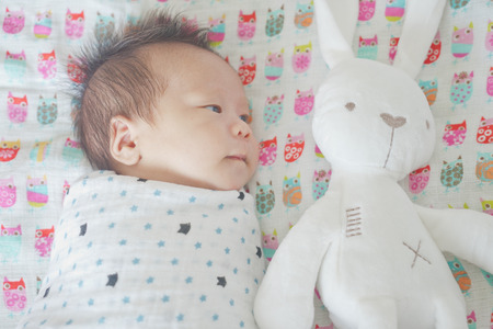 Photo pour Cute adorable newborn baby boy wrapped or swaddle in a blanket, sleeping and sometime both eyes open in kids bed - image libre de droit