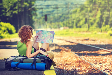 Foto de Girl wearing backpack holding map, waiting for a train. - Imagen libre de derechos