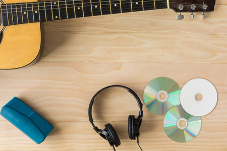 Photo for Acoustic guitar, cd and headphone on wooden background - Royalty Free Image