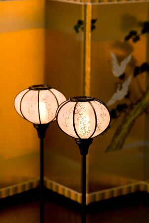 Japanese lantern in front of gold folding screen
