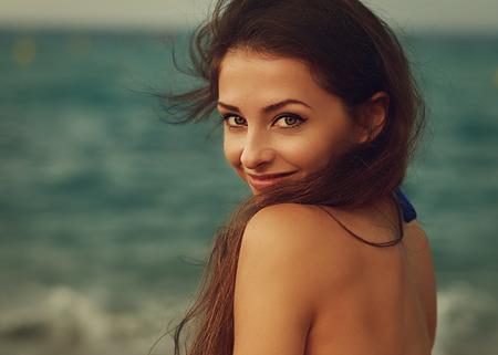 Photo pour Smiling young woman looking happy on sea background. Closeup vintage portrait - image libre de droit