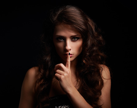 Foto de Beautiful make-up woman showing silence sign the finger near lips on black background - Imagen libre de derechos