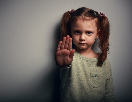 Foto de Angry kid girl showing hand signaling to stop useful to campaign against violence and pain on dark background. Closeup portrait - Imagen libre de derechos