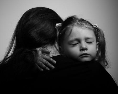 Foto de Depression daughter hugging her mother with sad face. Closeup portrait black and white - Imagen libre de derechos