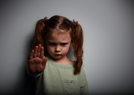 Foto de Kid girl showing hand signaling to stop violence and pain and looking down on dark background with empty copy space - Imagen libre de derechos