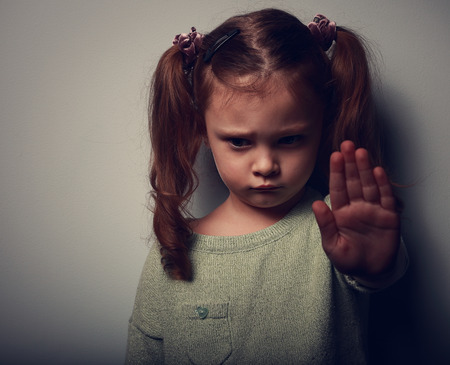 Foto de Kid girl showing hand signaling to stop violence and pain and looking down on dark background. Closeup color portrait - Imagen libre de derechos