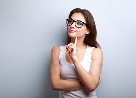 Photo pour Thinking young woman in glasses looking on empty space background - image libre de droit