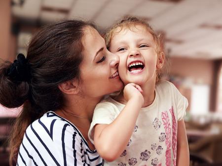 Foto de Beautiful young mother hugging her joying happy daughter indoor background - Imagen libre de derechos