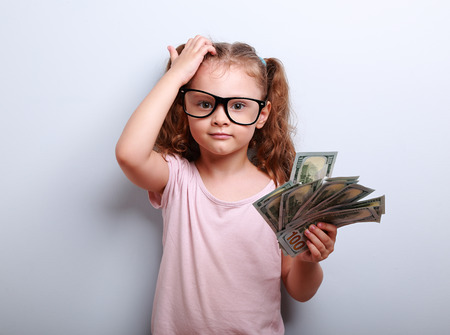 Photo pour Small professor in eye glasses scratching head, holding money and thinking how earring more. Kid have an big idea. Emotional portrait on blue background with empty copy space - image libre de droit