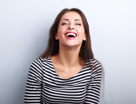 Photo for Happy natural laughing young casual woman with wide open mouth and closed eyes on blue background - Royalty Free Image