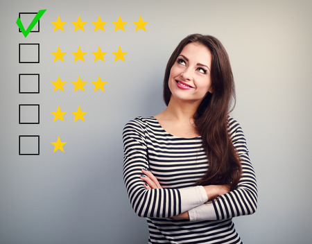 Foto de The best rating, evaluation. Business confident happy woman voting to five yellow star to increase ranking. On grey background - Imagen libre de derechos