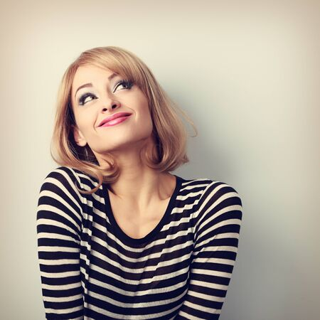 Photo for Fun beautiful thinking blond young woman in sweater looking up. Vintage toned portrait - Royalty Free Image