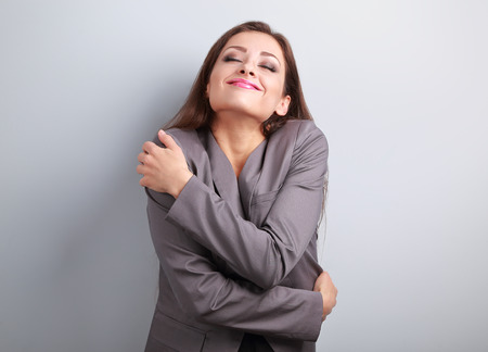 Photo pour Happy business woman hugging herself with natural emotional enjoying face. Love concept of yourself - image libre de droit
