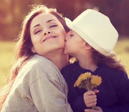 Foto de Happy daughter kissing her enjoying mother on summer sunny background - Imagen libre de derechos
