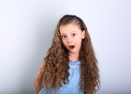 Photo for Excited surprising kid girl with wide open mouth and big eyes looking on blue empty copy space background. - Royalty Free Image