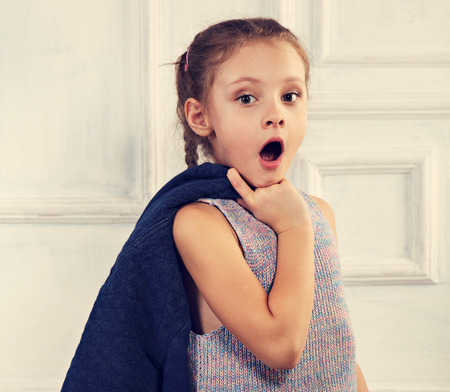 Photo for Surprising kid girl with opened mouth looking and holding blue jacket. Closeup toned portrait - Royalty Free Image