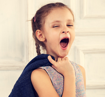 Photo for Kid girl in fashion blouse posing in studio and wanting to sleep and yawning - Royalty Free Image