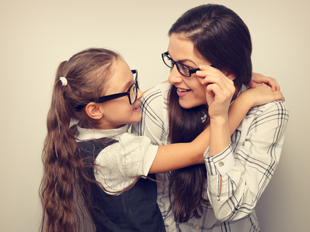 Photo for Happy surprising mother and excite kid in fashion glasses looking each other and cuddling on empty copy space blue background. - Royalty Free Image