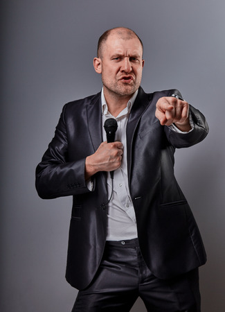 Photo for Fun emotional moving happy performer man presenting the show holding microphone in hand and showing the finger the choosing sign on grey color background. Closeup portrait - Royalty Free Image