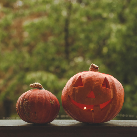 Photo for Background Halloween pumpkin on a cozy window sill with a red plaid. Whole pumpkin and sparkler outdoors. Happy Halloween! Autumn is cozy. rain outside. - Royalty Free Image
