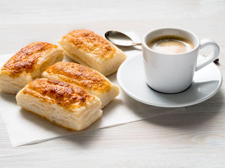Photo for morning Breakfast with fresh rolls of puff pastry and Cup of coffee on white wooden table. Side view, the light of day. - Royalty Free Image