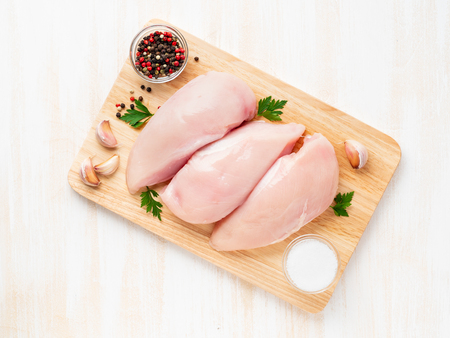 Foto de raw chicken breast fillet with spices on a wooden board on white wooden table, top view - Imagen libre de derechos