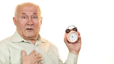 Photo for Senior man looking shocked checking time on alarm clock - Royalty Free Image