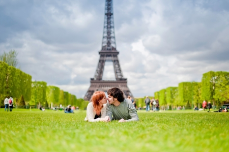 Loving couple lying on the grass on the Champ de Mars in Paris with the Eiffel Tower in the Background