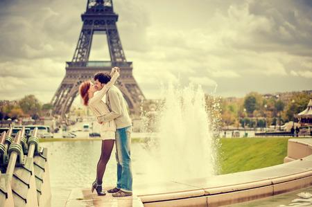 Foto de Lovers kissing in Paris with the Eiffel Tower in the Background - Imagen libre de derechos