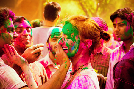 Foto de Woman tourist celebrating the Indian festival of Holi with the local Indian population. People at the holi festival in India. Holi, or Holli,is a spring festival celebrated by Hindus, Sikhs and others. The main day, Holi, is celebrated by people throwing  - Imagen libre de derechos