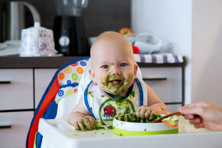 Photo for Feeding. Adorable baby child eating with a spoon in high chair. Baby's first solid food - Royalty Free Image