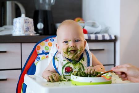 Foto de Feeding. Adorable baby child eating with a spoon in high chair. Baby's first solid food - Imagen libre de derechos