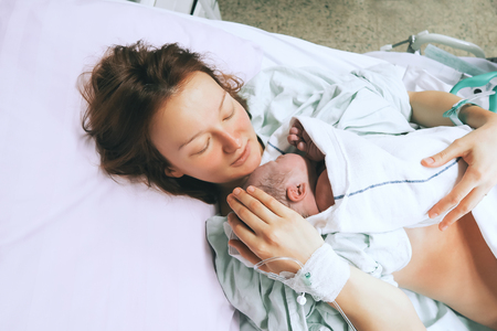 Photo pour Mother holding her newborn baby child after labor in a hospital. Mother giving birth to a baby boy. Parent and infant first moments of bonding. - image libre de droit