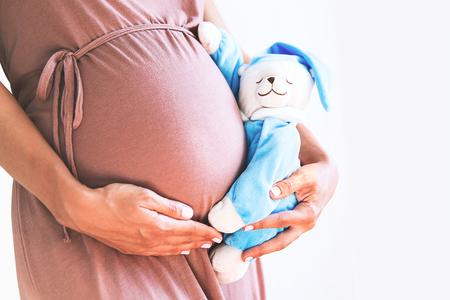 Foto de Close-up pregnant woman's belly with teddy toy bear. Pregnancy, parenthood, preparation and expectation concept. - Imagen libre de derechos