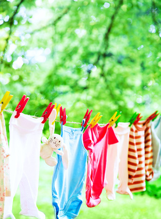 Photo pour Baby cute clothes hanging on the clothesline outdoor. Child laundry hanging on line in garden on green background. Baby accessories. - image libre de droit