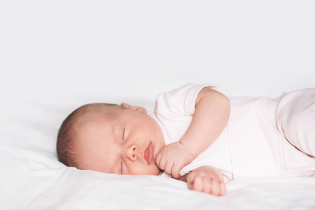 Photo pour Sleeping newborn baby in a bodysuit on white blanket background. Beautiful portrait of little child girl 14 days, two week old. - image libre de droit