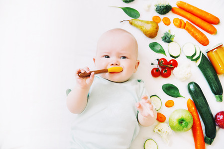 Photo pour Healthy child nutrition, food background, top view. Baby 8 months old surrounded with different fresh fruits and vegetables on white background. Baby first solid feeding - image libre de droit