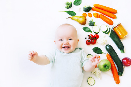 Photo pour Healthy child nutrition, food background, top view. Smiling baby 8 months old surrounded with different fresh fruits and vegetables on white background. Baby first solid feeding - image libre de droit