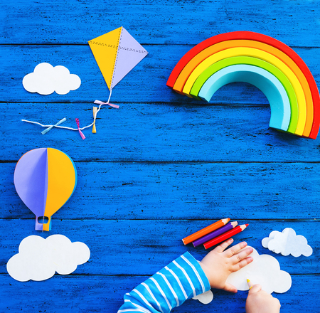Photo pour Creative children's waldorf or montessori school concept. Paper crafts, colored pencils, wood rainbow with child hands on blue table. Kids art class, kindergarten, preschool background with copy space - image libre de droit