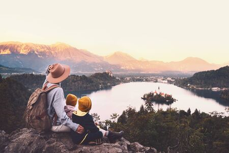Foto de Journey Slovenia with kids. Family travel Europe. Hiker woman with children on Bled Lake among nature and Alps mountains. Traveling mother with backpack with her kids at autumn or winter vacation - Imagen libre de derechos