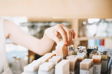 Foto de Woman with cotton bag buying personal hygiene items in zero waste shop. Eco Organic Cosmetics. Girl choose toiletries products in plastic free store. Minimalist lifestyle. Shopping at local businesses - Imagen libre de derechos